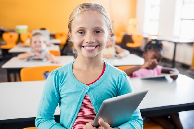 A cute pupil posing with tablet pc