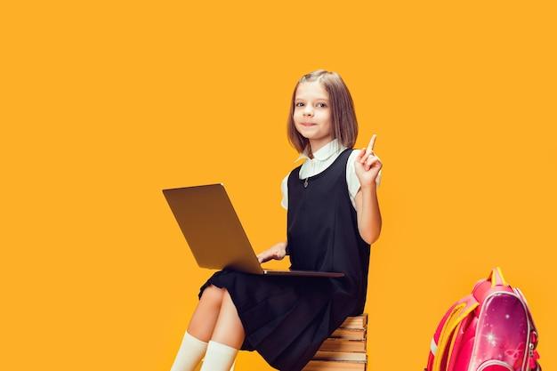 귀여운 학생은 노트북이 있는 책 더미에 앉아 검지 손가락 어린이 교육으로 손을 들어 올립니다