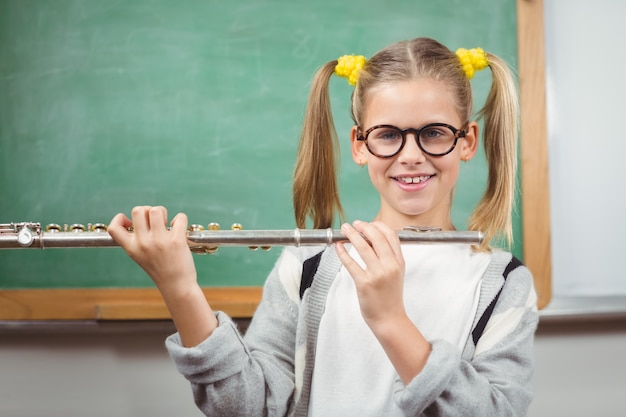 Cute pupil with flute in a classroom
