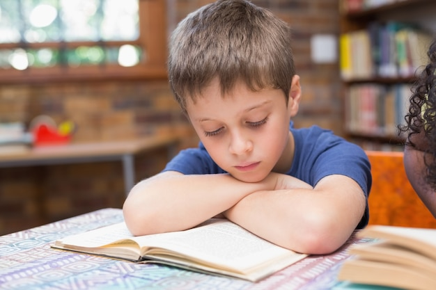 Cute pupils reading books in library