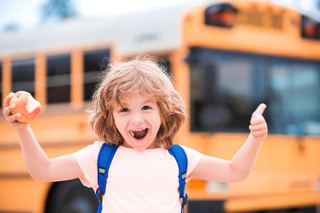 小学校の外のスクールバスでカメラに向かって微笑んでいるかわいい生徒たち。手で前向きなジェスチャーをしているサインを持った子供、笑顔で幸せな親指。