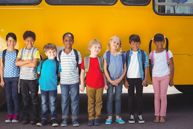 Cute pupils smiling at camera by the school bus