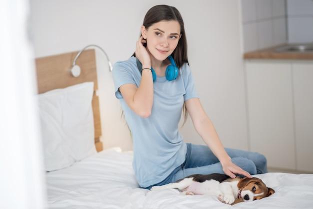 Милый щенок. владелец домашнего животного сидит на кровати и чувствует себя счастливым со своим питомцем