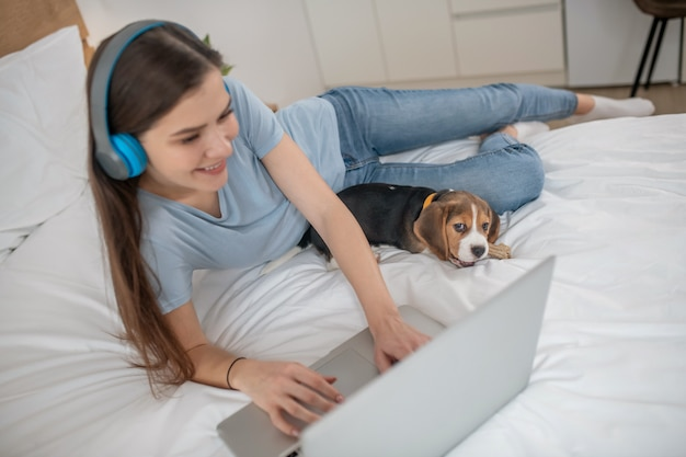 Милый щенок лежит рядом со своей хозяйкой, пока она что-то смотрит онлайн
