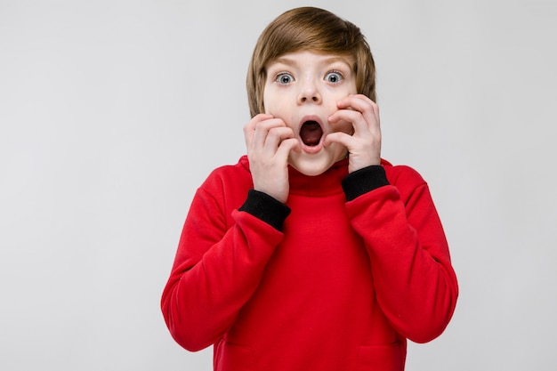 Cute puzzled astonished little boy with open mouth on grey