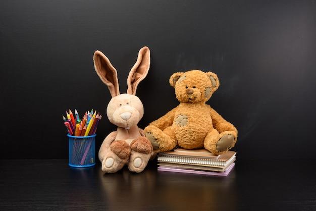 Милый кролик и коричневый плюшевый мишка сидят на фоне черной меловой доски, снова в школу