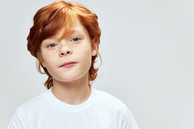 Милый рыжий мальчик в белой футболке