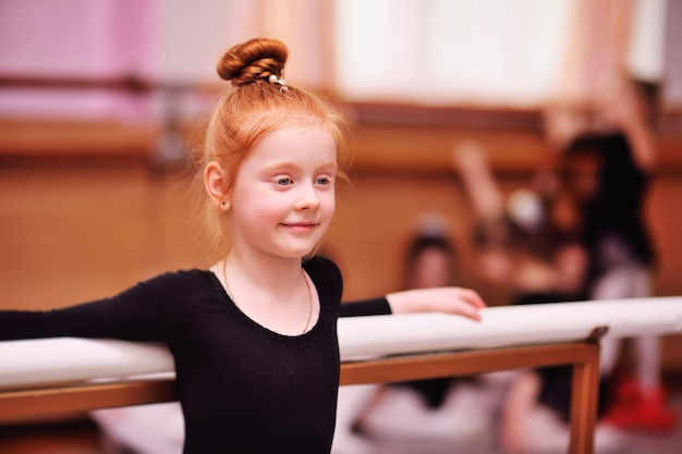 かわいい赤い髪の少女バレリーナストレッチと分割を行う