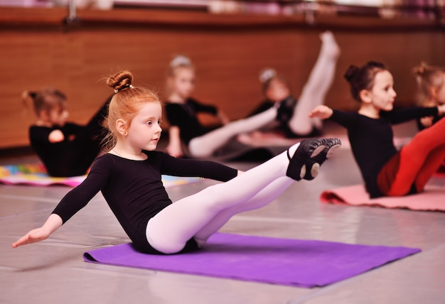 A cute red-haired girl ballerina stretching and doing the splits