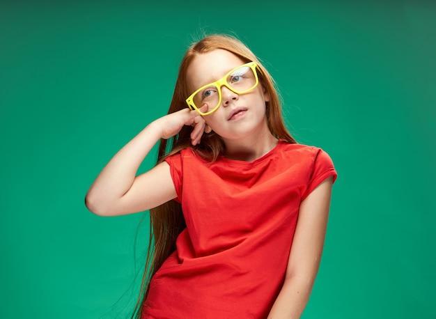 Симпатичная рыжеволосая девушка, жестикулирующая руками, детство, зеленая школа фона. фото высокого качества