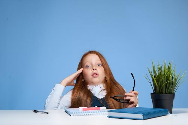 テーブルの学校教育に座っているかわいい赤毛の女の子の学生