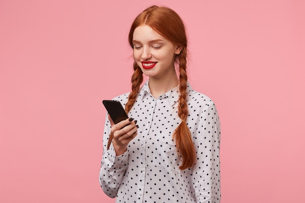 Симпатичная рыжеволосая девушка с косичками держит в руке телефон и читает сообщение и радостно улыбается, довольная, стоя полоборота в изоляции
