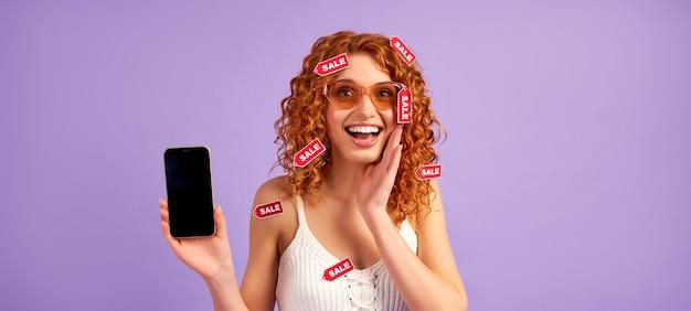 곱슬 머리와 보라색에 고립 된 빈 스마트 폰 화면을 보여주는 판매 레이블 귀여운 빨간 머리 소녀