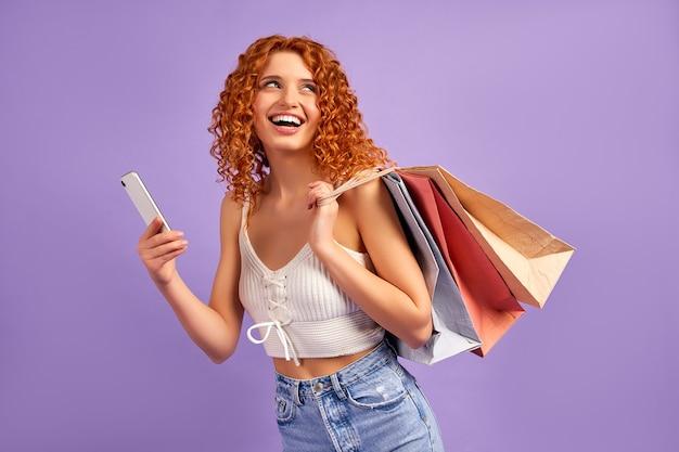 Симпатичная рыжеволосая девушка с кудрями и хозяйственными сумками и смартфоном, изолированными на фиолетовом. онлайн шоппинг. распродажа