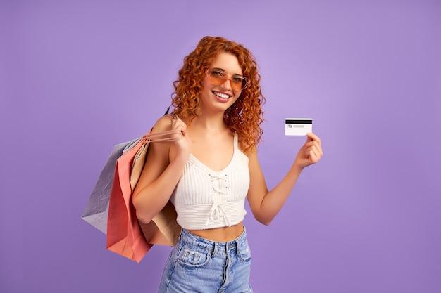 Милая рыжеволосая девушка с кудрями и хозяйственными сумками, держащая кредитную карту, изолированную на фиолетовом. онлайн шоппинг. распродажа