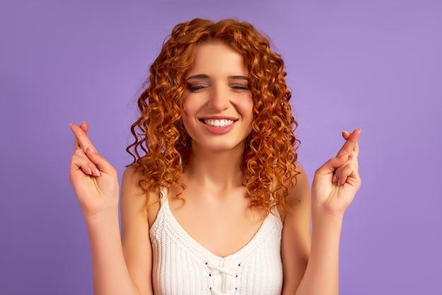 Милая рыжеволосая девушка с кудрями закрыла глаза, скрестив пальцы на удачу, изолирована на фиолетовом