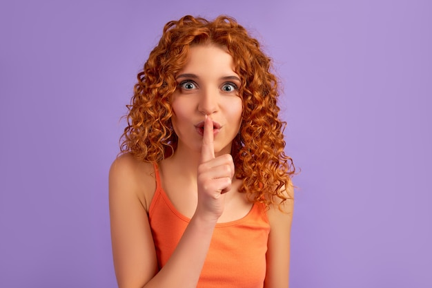 Cute red-haired girl with curls holds her finger to her lips, speaking softly, shh isolated on purple