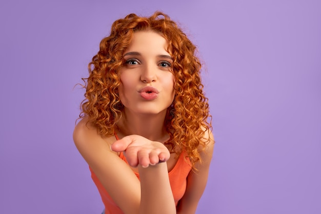 Cute red-haired girl with curls sends an air kiss isolated on purple