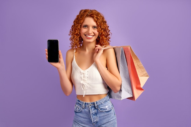 Cute red-haired girl with curls and shopping bags shows blank screen of smartphone isolated on purple. online shopping. sale