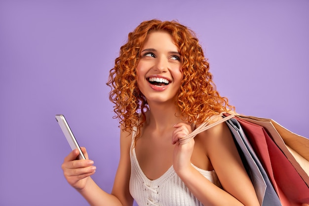 Cute red-haired girl with curls and shopping bags and smartphone isolated on purple. online shopping. sale