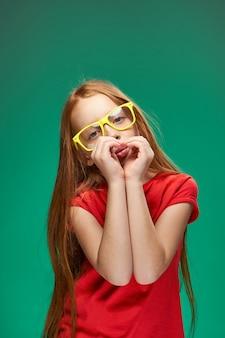 Милая рыжеволосая девушка в очках, жестикулируя руками школьного детства зеленом фоне. фото высокого качества