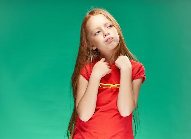 Симпатичная рыжеволосая девушка в очках на голове в красной футболке