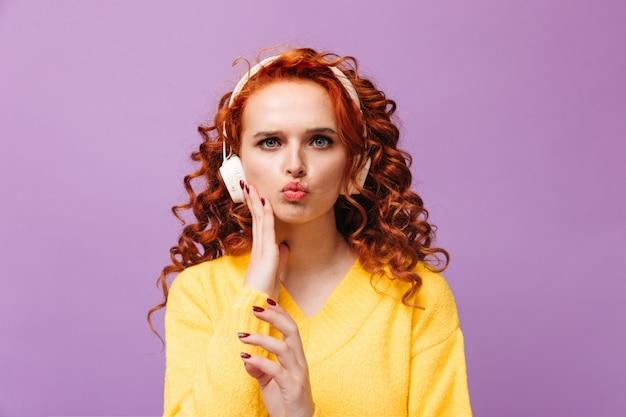 Una ragazza carina dai capelli rossi con un maglione giallo ha gonfiato le guance e ascolta musica con le cuffie