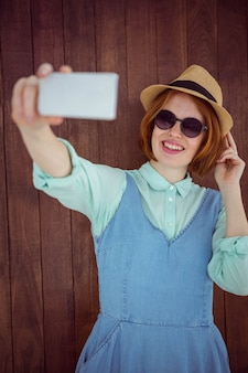 Cute red haired hipster taking a selfie