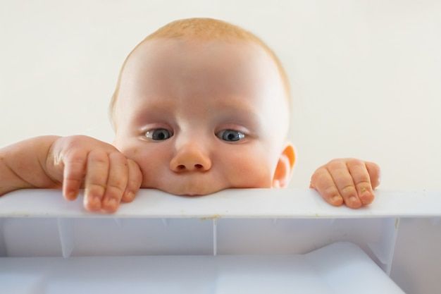 プラスチック製のボードをかむかわいい赤毛の空腹の赤ちゃん。テーブルから見てそれを保持している好奇心が強い新生児のクローズアップビュー。幼年期および幼児期の概念