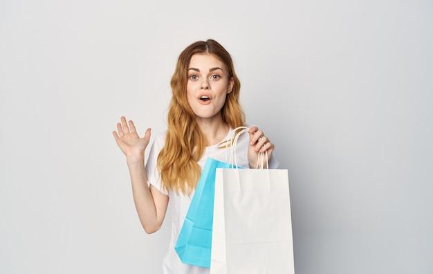 쇼핑 손에 패키지와 흰색 티셔츠에 귀여운 빨간 머리 여자