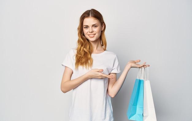 패키지와 흰색 티셔츠에 귀여운 빨간 머리 여자