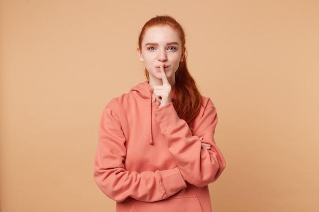 포니 테일에 모인 머리카락을 가진 귀여운 빨간 머리 여자가 멋지게 바람둥이로 입술에 검지 손가락으로 침묵 제스처를합니다.