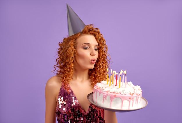 Симпатичная рыжеволосая женщина с кудрями в блестящем платье и праздничной кепке держит торт и задувает свечи, изолированные на фиолетовом