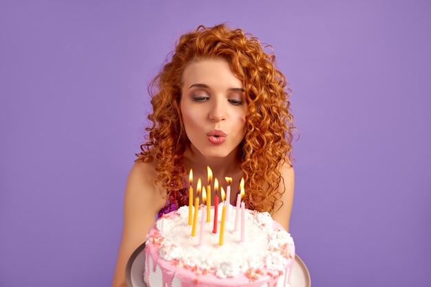 Милая рыжеволосая женщина с кудрями в блестящем платье держит торт и задувает свечи, изолированные на фиолетовом