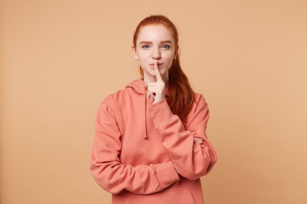 Cute red-haired woman with a hair gathered in ponytail nicely flirts, makes a silence gesture with index finger on her lips
