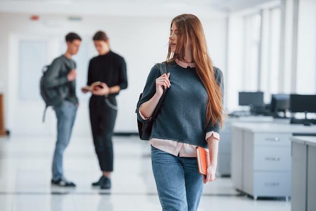 귀여운 redhaired 소녀. 휴식 시간에 사무실에서 걷는 젊은 사람들의 그룹입니다.