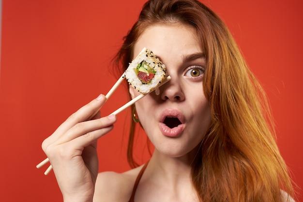 Симпатичная рыжеволосая женщина делает рулеты палочками для еды и закуски из морепродуктов