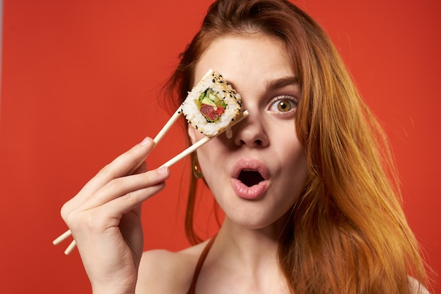Cute redhaired woman chopsticks rolls and seafood snack