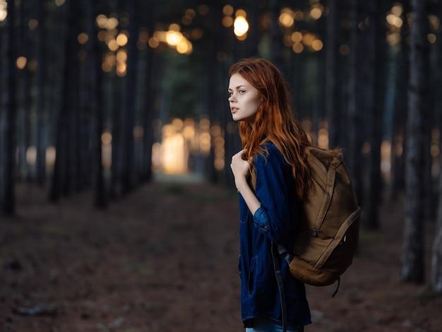 かわいいredhaired女性ハイカーバックパック森旅行