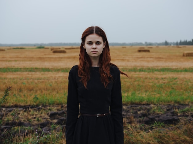 フィールド旅行ファッションの黒のドレスでかわいいredhaired女性