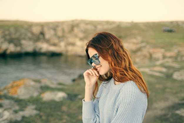 屋外で眼鏡をかけているかわいいredhaired女性新鮮な空気の旅