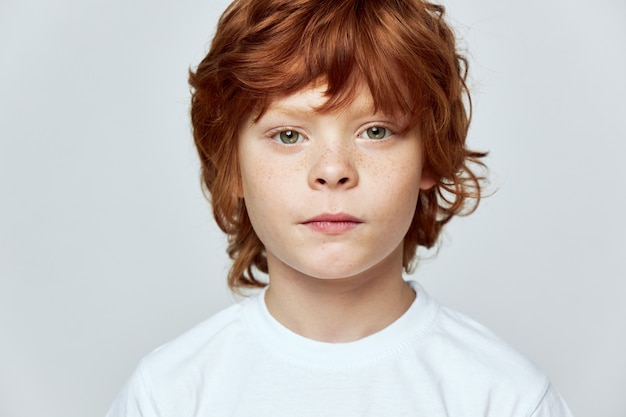 Cute redhead boy freckles on his face cropped view