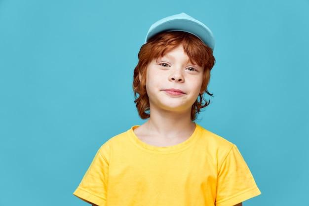 Симпатичный рыжий мальчик смотрит вперед, желтая футболка, синяя кепка, обрезанный вид