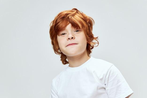 白いtシャツでポーズをとってかわいい赤毛の少年
