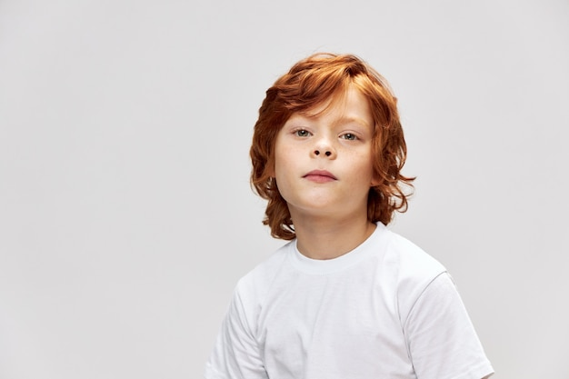 Cute redhead boy in white t-shirt close-up gray isolated