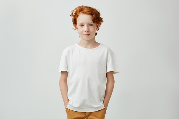 Cute redhead boy with good-looking hairstyle in white t-shirt holding holding hands in pockets, gently smiling