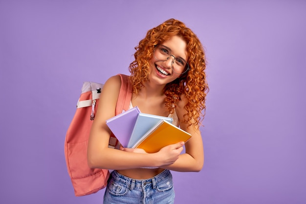 Cute redhead curly girl student teenager with a backpack holds notepads and notebooks isolated on a purple wall.