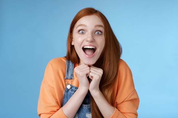 Cute redhead european girl blue eyes freckles reacting amused shocking rumor lift eyebrows drop jaw surprised smiling excited picked get role theatre play rejoicing astonished blue background