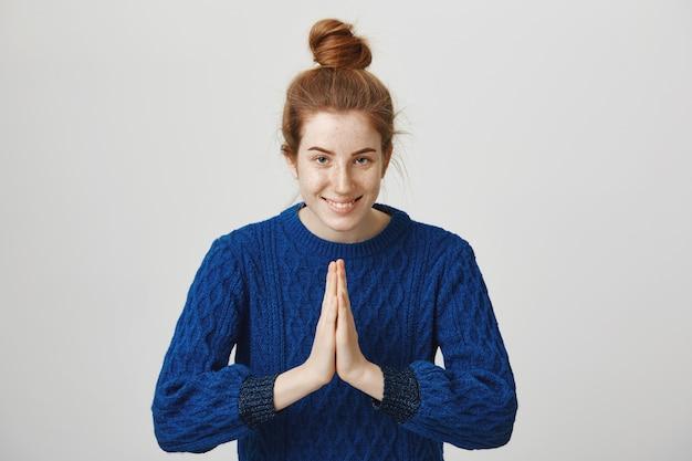 Yoga di pratica femminile rossa carina, inchinandosi con gesto di namaste