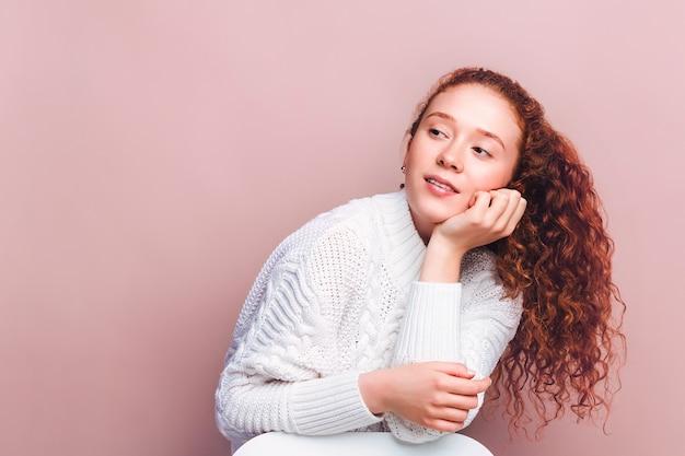 흰색 스웨터에 귀여운 빨간 머리 소녀 미소와 텍스트를위한 공간을 찾습니다